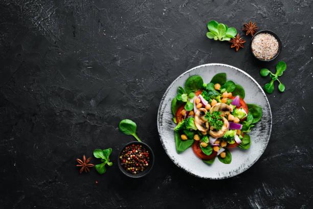 Salada com cogumelos, espinafre, ervilhas turcas e cebola em uma placa em um fundo de madeira vista superior. Espaço livre para o seu texto. Lisa Lopes - foto de acervo