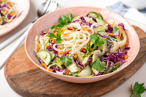 Vegetarian food. Salad with noodles, vegetables and sesame seeds in a bowl close-up. Tasty and healthy food.