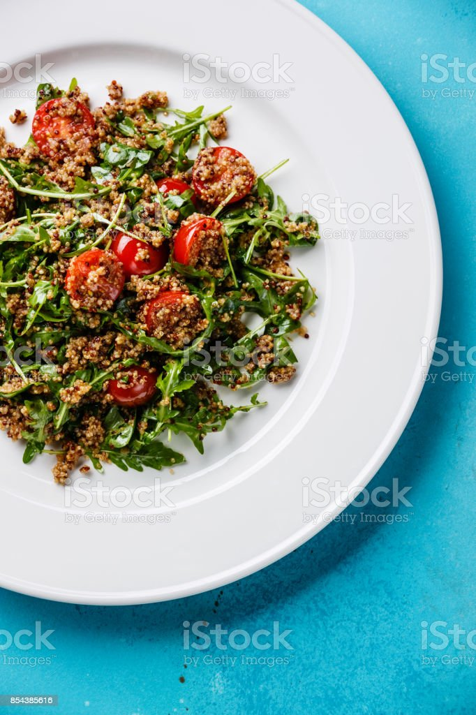 Salad with quinoa, tomato and arugula stock photo