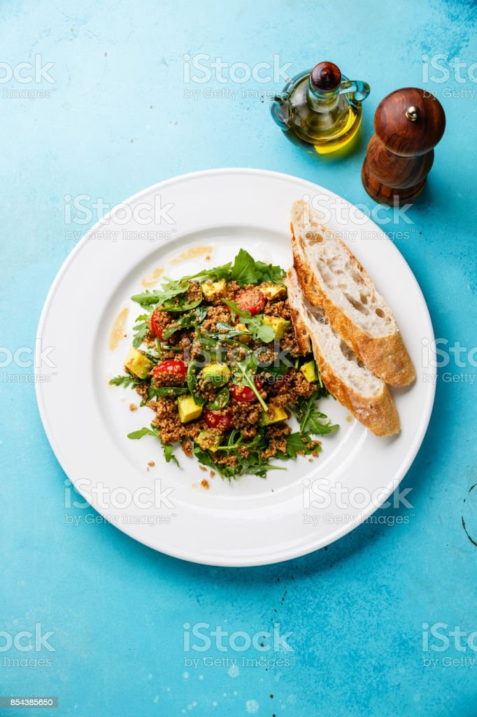 Salad with quinoa, tomato, avocado, spinach and arugula stock photo