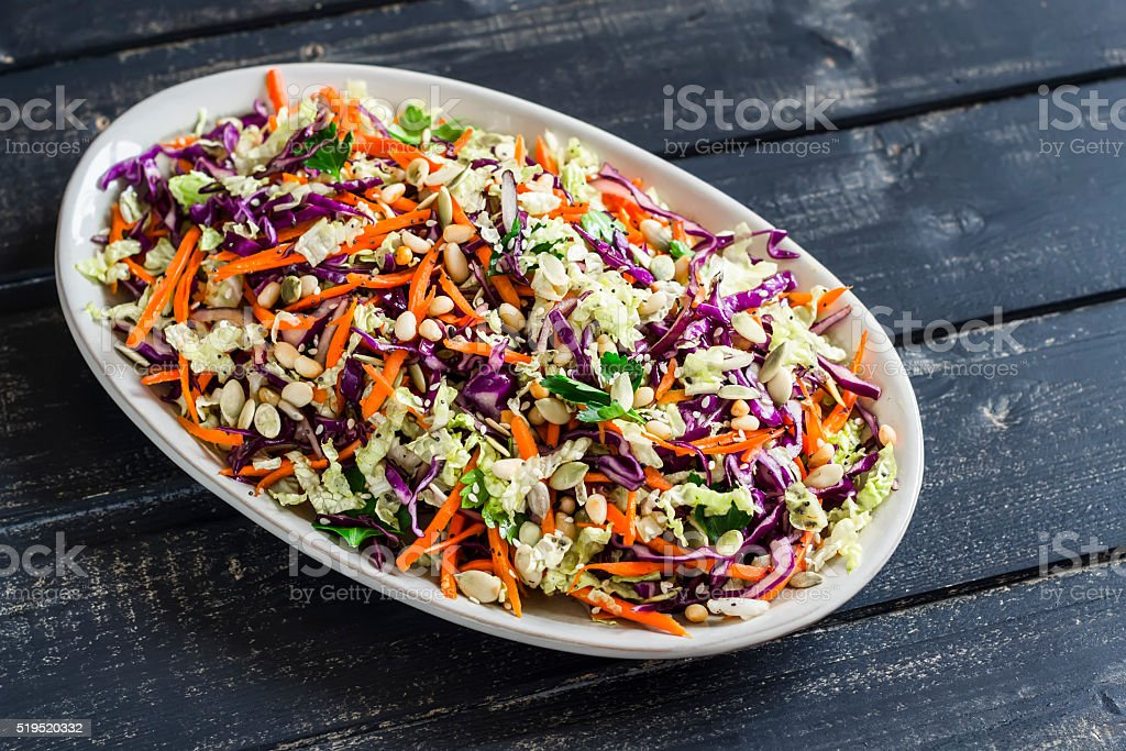 salad with red cabbage, carrots, sweet peppers, herbs and seeds stock photo