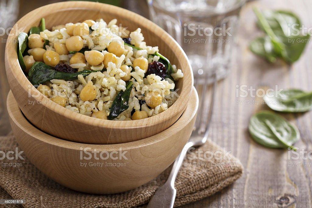 Ensalada con arroz, los garbanzos, espinacas, pasas - Foto de stock de Ajo libre de derechos