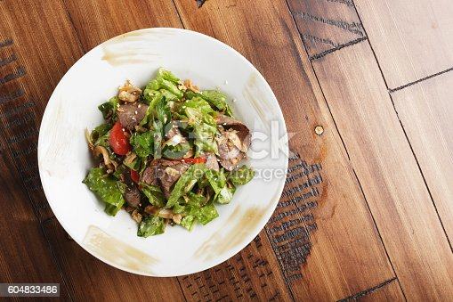 Salad with roast beef in a white plate. Brown wooden background