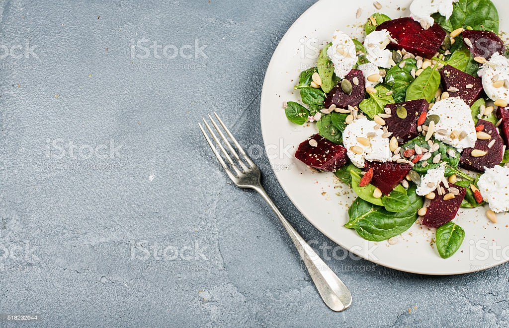 Salad with roasted beetroot, spinach, soft goat cheese and seeds stock photo