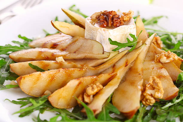 Salad with roasted pears, walnuts and goat cheese stock photo