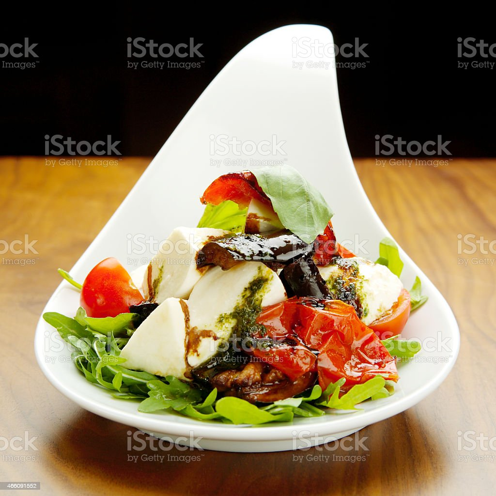 Salad with rocket, cheese and tomato, close up stock photo