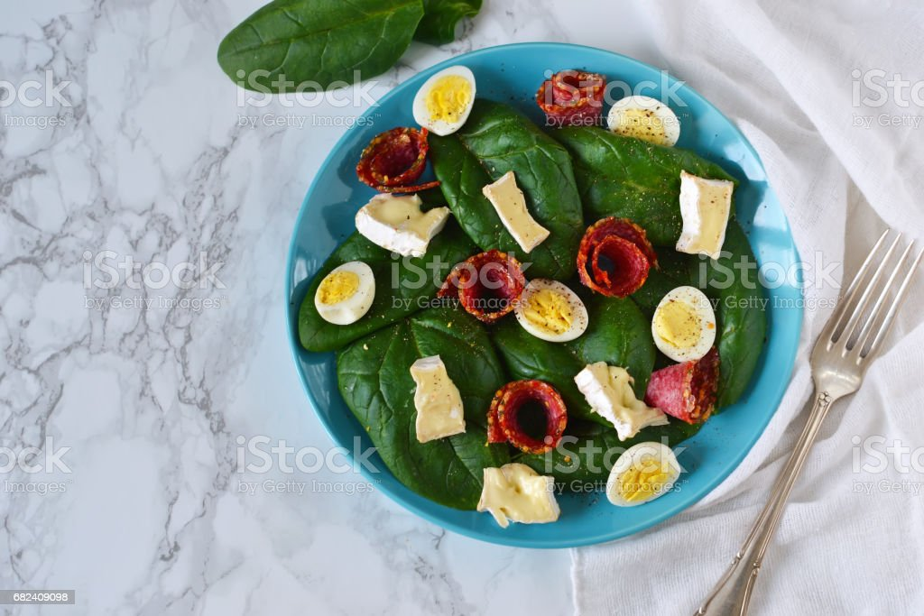 Salad with spinach, brie cheese and quail eggs on a marble background royalty-free stock photo