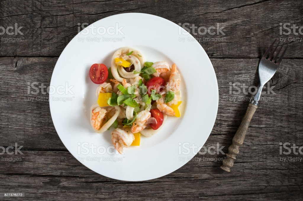 Salad with squid rings, shrimps, pepper and tomatoes stock photo