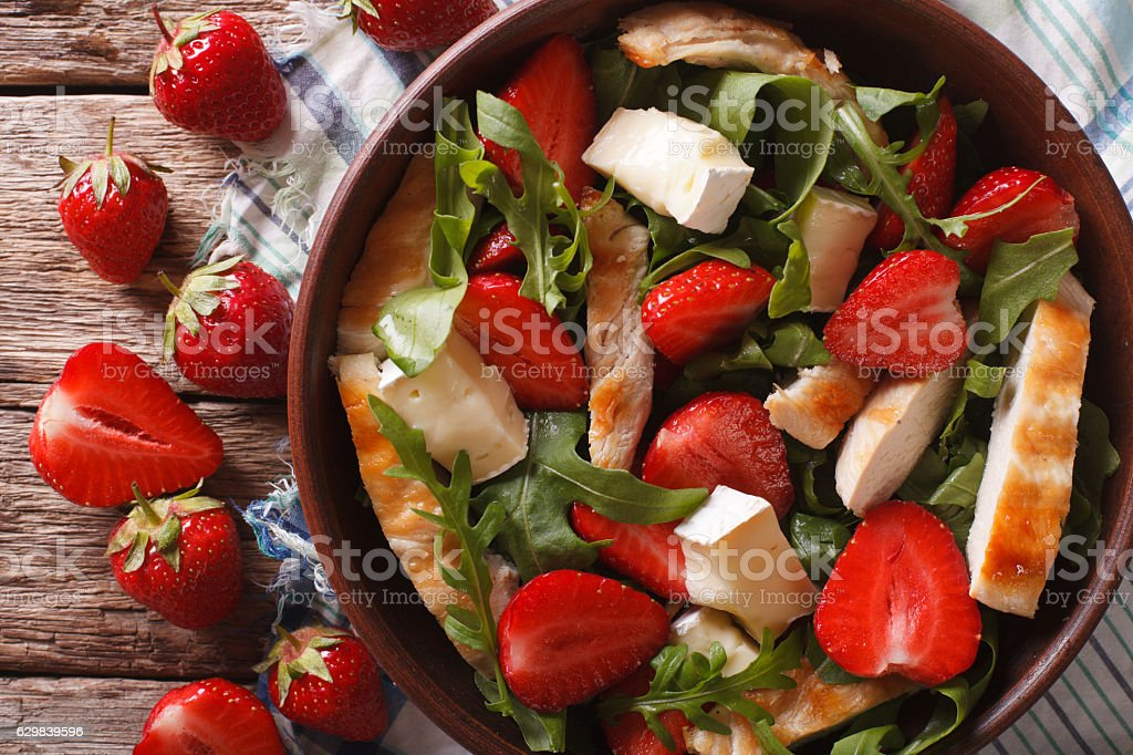 salad with strawberries, chicken, cheese and arugula closeup stock photo
