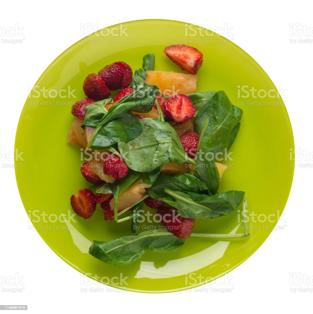 salad with strawberries, pineapple and spinach on a lime plate. fruit...