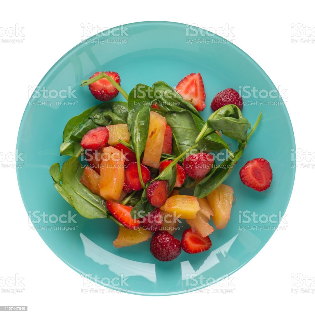 salad with strawberries, pineapple and spinach on a turquoise plate....