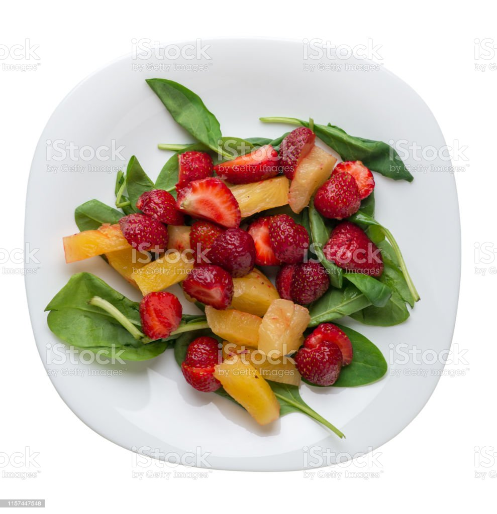 salad with strawberries, pineapple and spinach on a white plate....