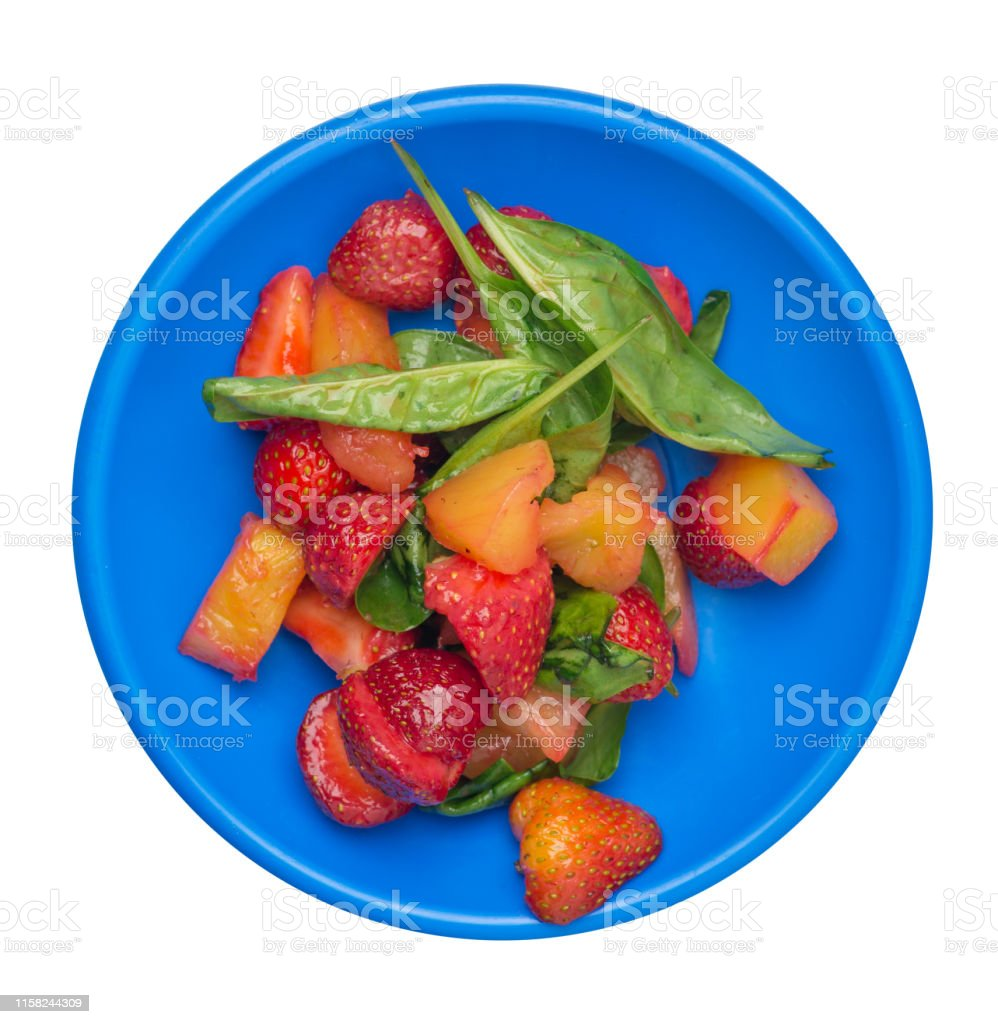 salad with strawberries, pineapple and spinach on a plate. fruit...