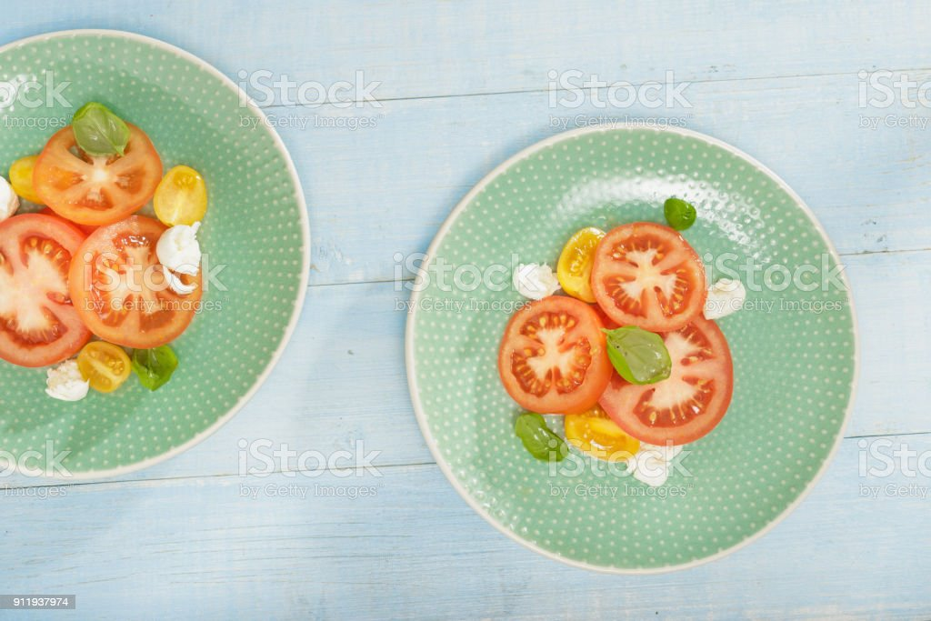 Salad with tomatoes and mozzarella cheese on blue wooden table, top view stock photo