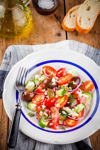 salad with tomatoes, cucumbers, olives, onions, feta and couscous - griechischer couscous salat stock-fotos und bilder