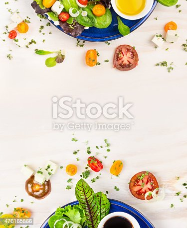 salad with tomatoes, greens, dressing and feta cheese in blue plate on white wooden background, top view frame