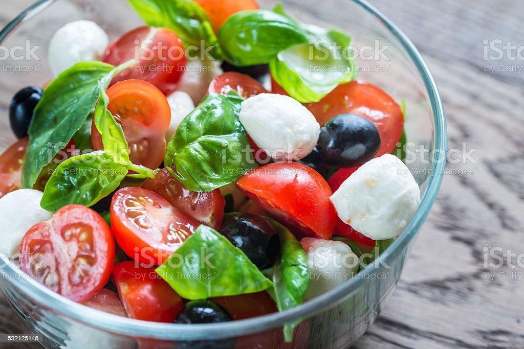 Salad with tomatoes, olives, mozzarella and basil stock photo