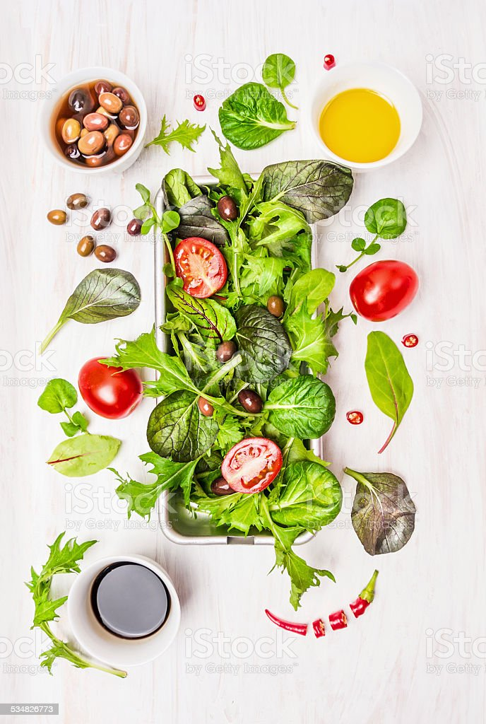 salad with tomatoes,olives,oil and vinegar on white wooden stock photo