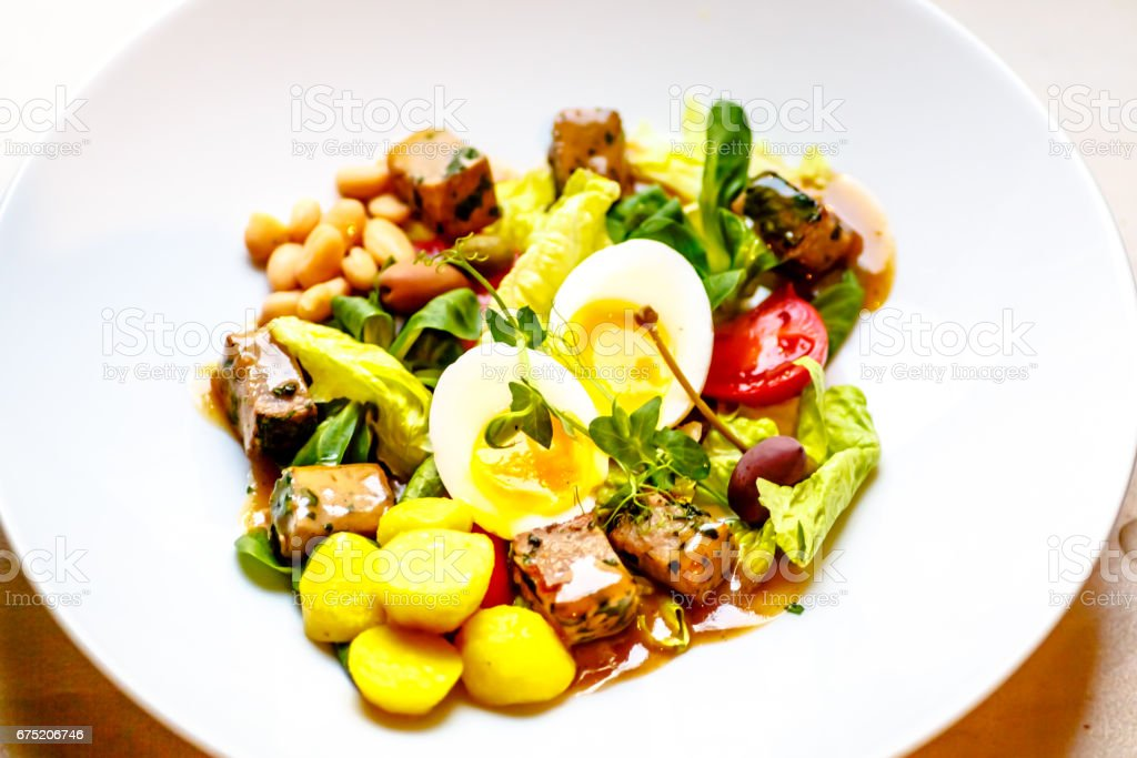 Salad with tuna, potatoes, capers, beans, egg and tomatoes. stock photo