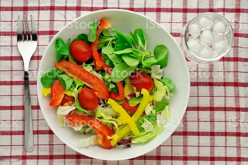 Salad with water glass on tablecloth - high angle view royalty-free stock photo