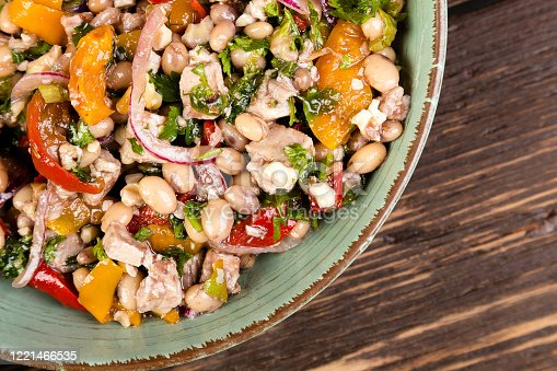 Salad with white beans, roasted red and yellow peppers and red onion in a vinaigrette dressing.