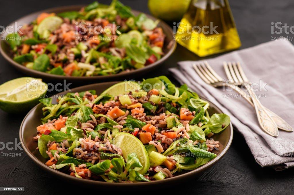 Salad with wild rice, papaya, lime and cucumber. stock photo