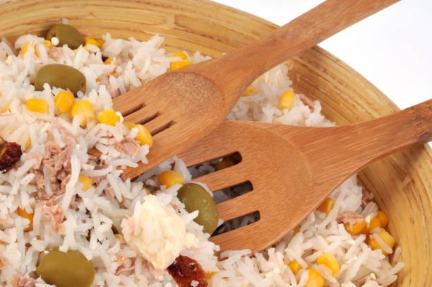 Salade de riz gros plan sur une salade de riz dans un saladier avec des couverts en bois riz stock pictures, royalty-free photos & images
