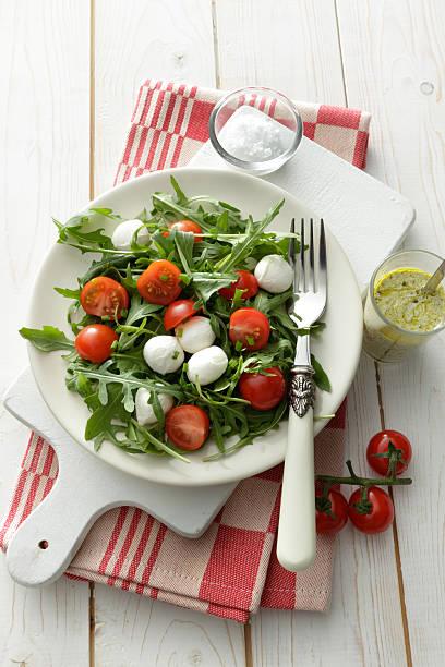 salate: arigula-salat mit kirsch tomatos, mozzarella und pesto - caprese salat stock-fotos und bilder