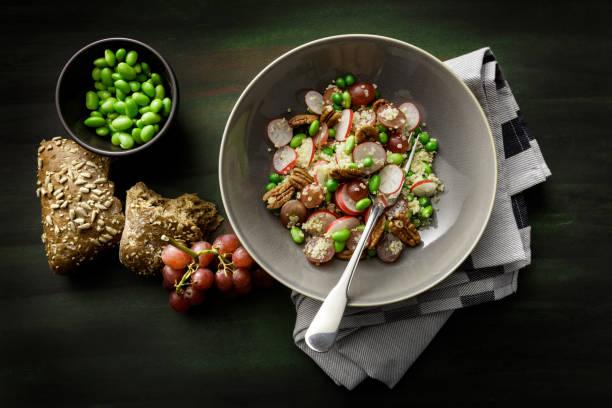 salate: quinoa salat mit radieschen, traube, sojabohnen und pekannüsse - radieschen salat stock-fotos und bilder