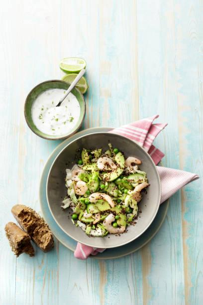 Salads: Quinoa Salad with Shrimps, Avocado, Iceberg Lettuce, Peas and Chives stock photo