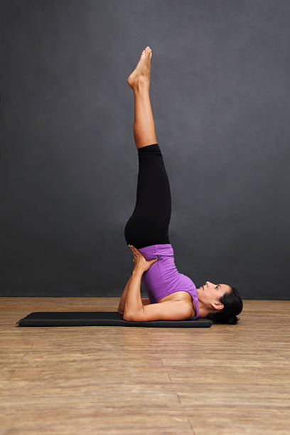 Salamba Sarvangasana Woman in a salamba sarvangasana yoga pose.See my people images serie by clicking on the image below: shoulder stand stock pictures, royalty-free photos & images
