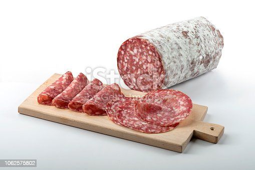 One piece of Finocchiona Salami and slices on Cutting board