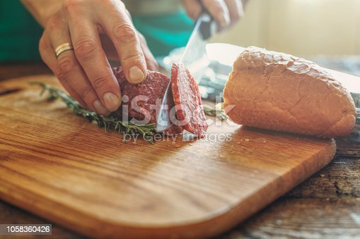 Human hands are cut into salami. Closep, making sandwiches.