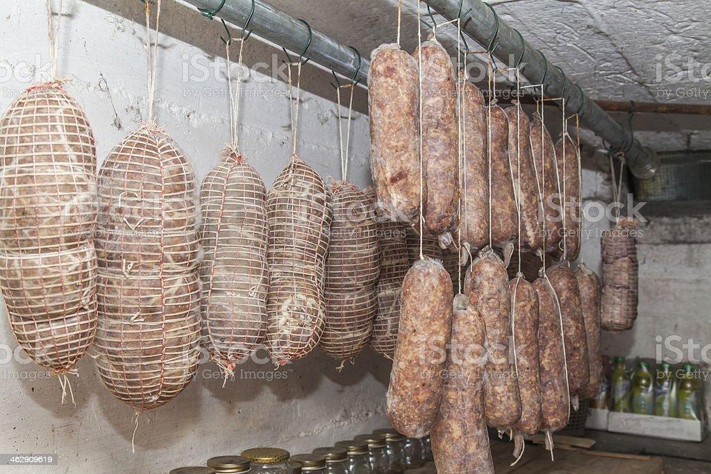 Salami Italian handmade hanging to mature in the cellar stock photo