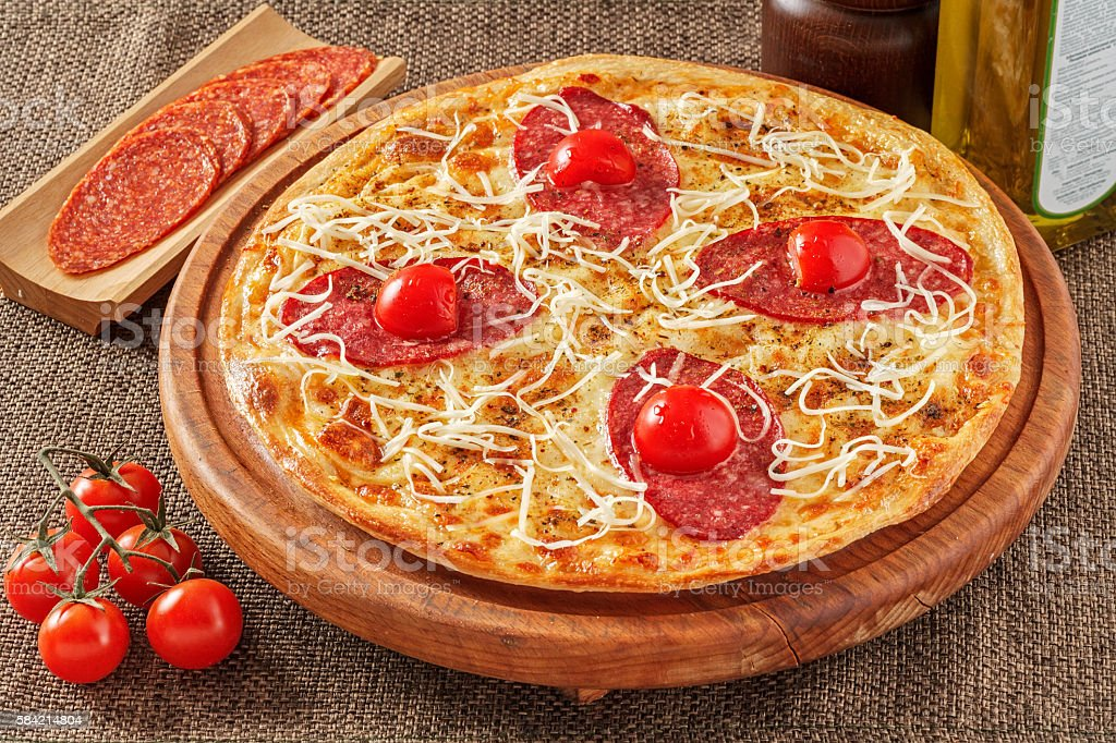 Salami pizza with cherry tomatoes stock photo