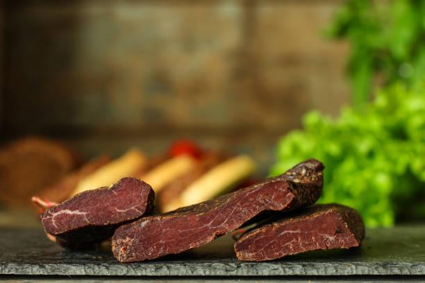 salami, carne salada seca - cortado con rodajas (venado). fondo de alimentos. vista superior con espacio de copia - fuet sausages fotografías e imágenes de stock