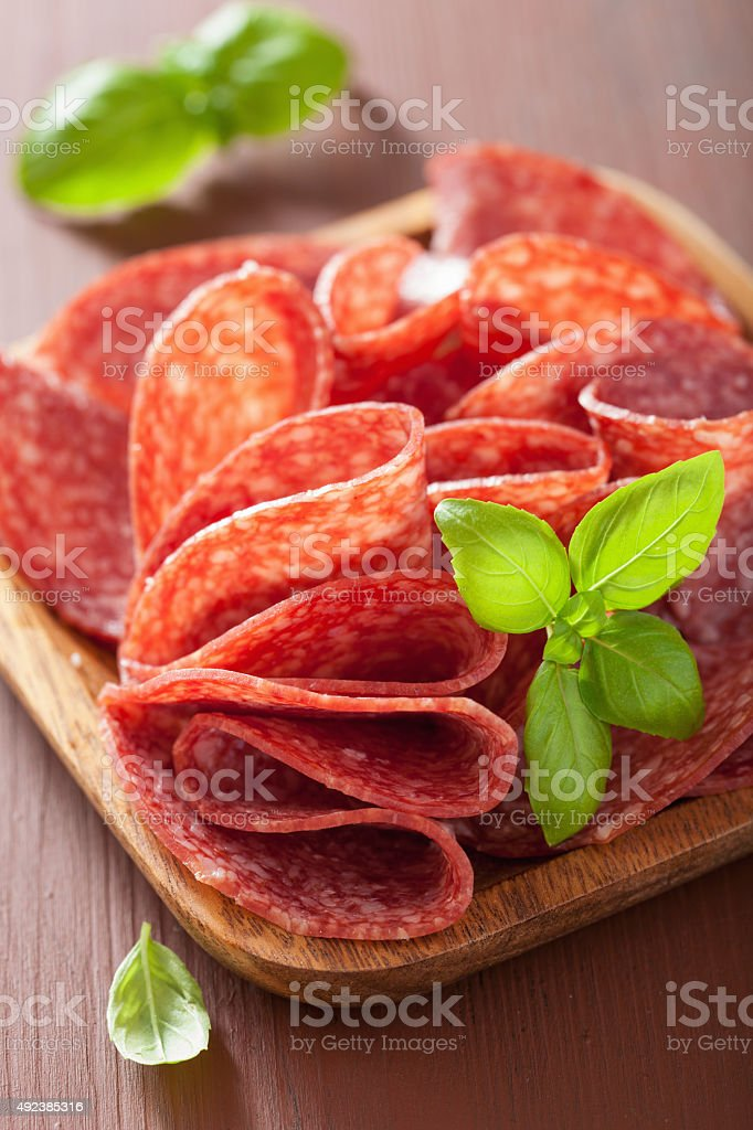 salami slices in wooden plate stock photo