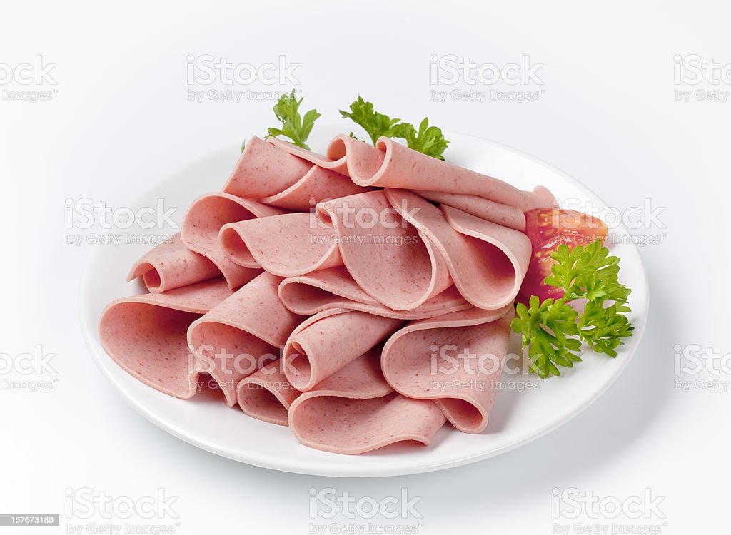 Salami slices on white plate stock photo