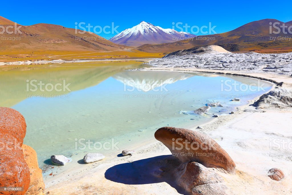 Salar de Talar and Miniques snowcapped Volcano - Turquoise lake mirrored reflection and Piedras rojas (red stones) rock formation at sunrise, Idyllic Atacama Desert, Volcanic landscape panorama – San Pedro de Atacama, Chile, Bolívia and Argentina border stock photo