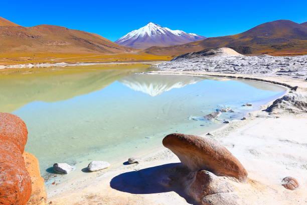 salar de talar 和 miniques 白雪皚皚的火山-綠松石湖鏡像反射和彼德拉斯羅哈斯 (紅石頭) 岩層在日出,田園詩般的阿塔卡馬沙漠,火山景觀全景 — — 聖佩德羅-德阿塔卡馬,智利、 bolívia 和阿根廷邊界 - 阿爾蒂普拉諾山脈 個照片及圖片檔