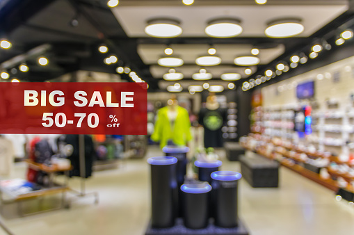 BIG Sale 50-70% off mock up advertise display frame setting over Abstract blurred photo of fashion store in shopping mall which have clothing bag and shoes, shopping concept