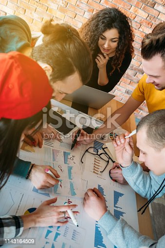 Sales analysis. Young business team at work studying graphs charts. Millennials brainstorming. Colleagues collaboration.