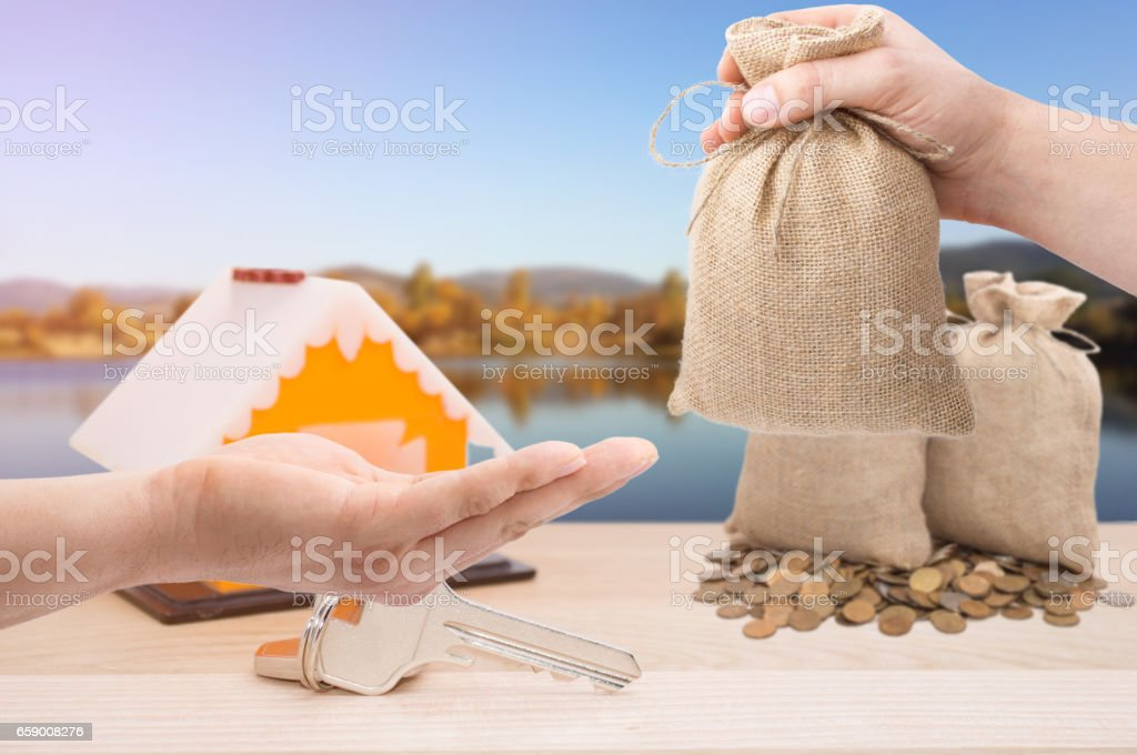 Sale and rental properties and cars  loans for real estate concept. Hand with bag dollar sign giving money to another royalty-free stock photo