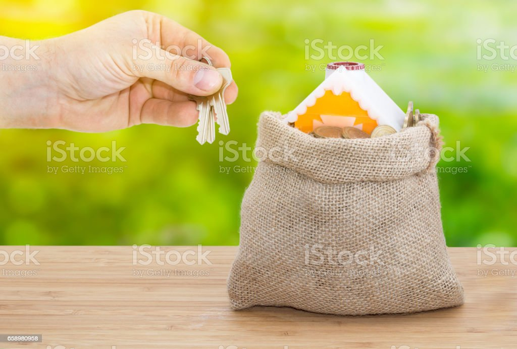 Sale and rental properties loans for real estate concept. A hand gives keys from home with coins in bag from sacking on wooden table royalty-free stock photo