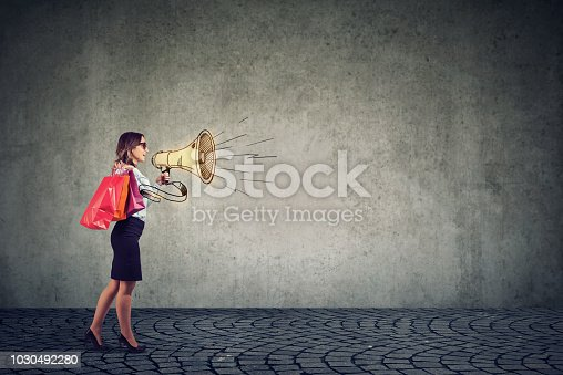 820421282istockphoto Sale concept, stylish young woman shouting in megaphone 1030492280