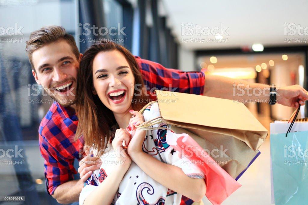 conceito de venda, consumismo e pessoas - casal jovem feliz com sacos de compras, andando no shopping. - foto de acervo
