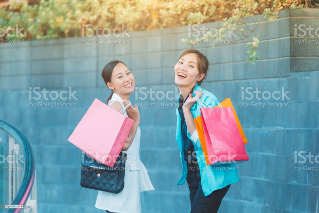 sale, consumerism and people concept - happy young women looking into shopping bags at shop in city. royalty-free stock photo
