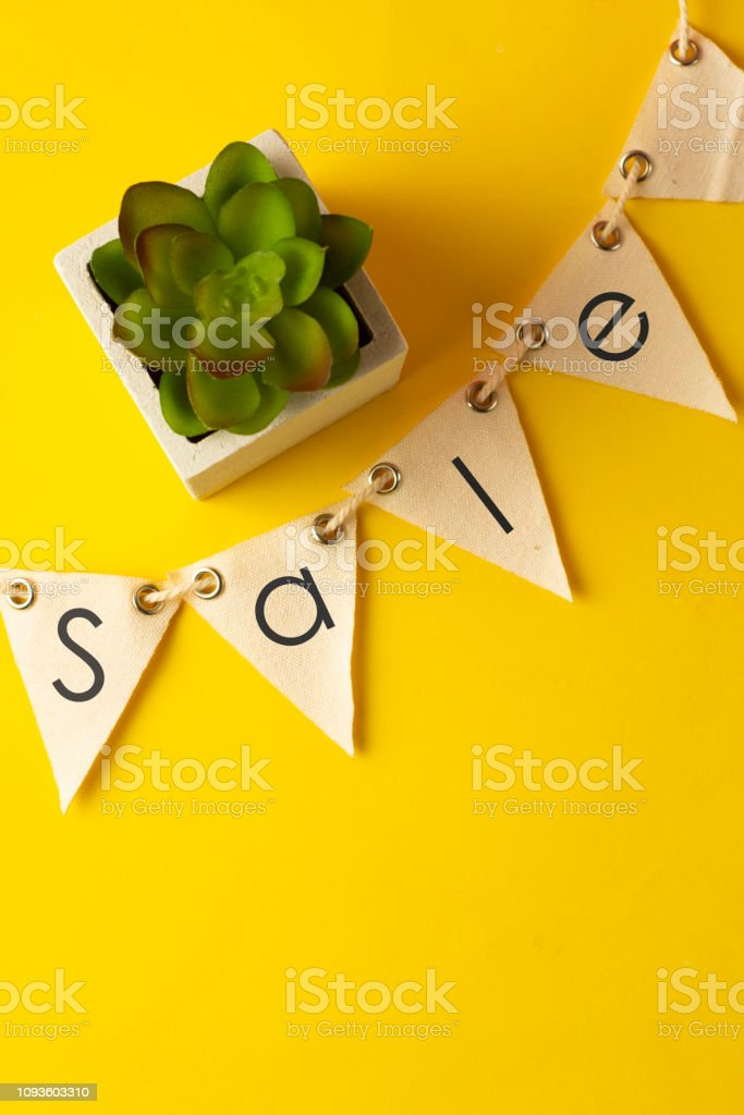 Sale inscription, word written on textile garland, over yellow background. Space for text, vertical image. stock photo