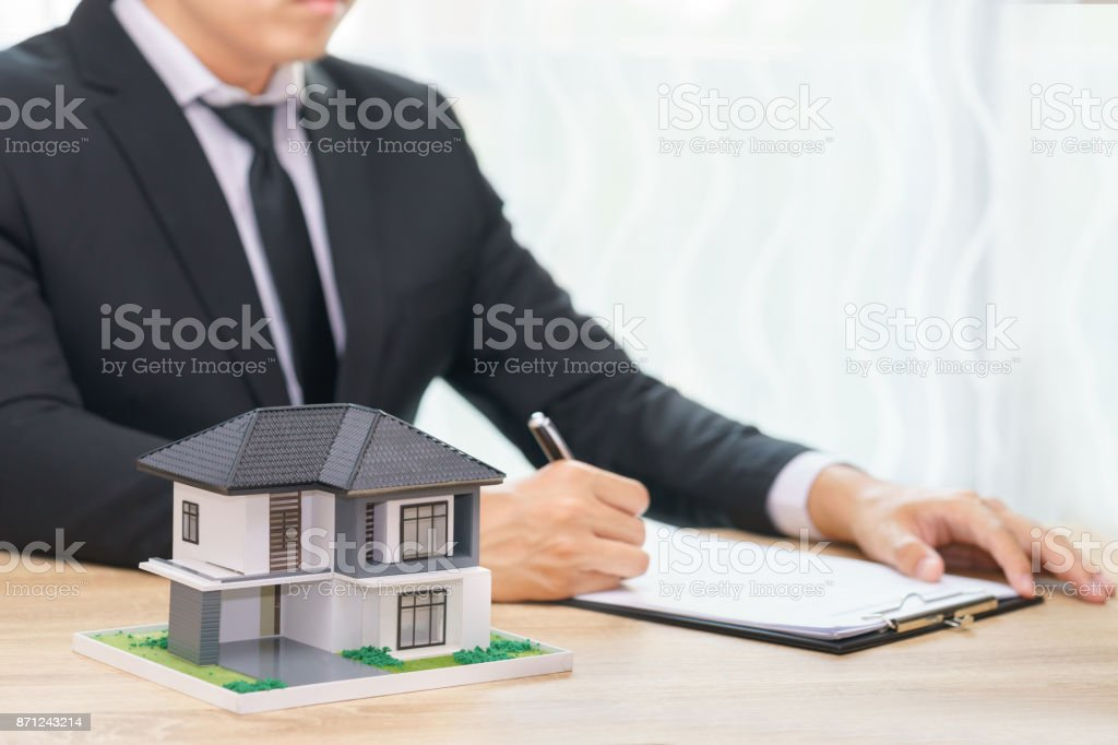 Sale man or businessman writing the reservation home agreement. stock photo