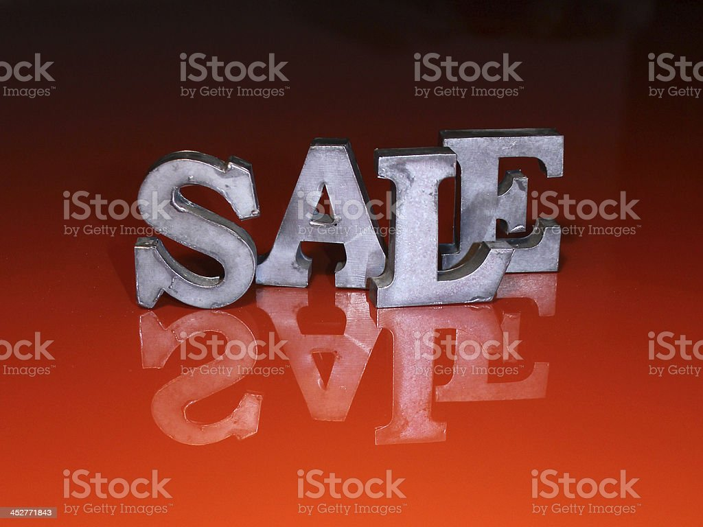 """Sale metal letters on red surface The word """"SALE"""" written in real metal letters. On red glas surface with glossy reflex. Glass - Material Stock Photo"""